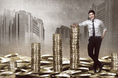 Asian business man leaning on the pile of coins Royalty Free Stock Images