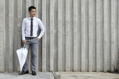 Asian business man leaning on a wall Stock Image