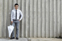 Asian business man leaning on a wall Royalty Free Stock Photography