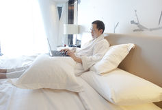 Asian business man lying in bed with his laptop Stock Photo