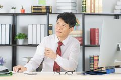 Asian business man at office. Happy middle aged, handsome, Asian, businessman, in white shirt, dark red necktie, working in his startup office, sending emails royalty free stock photos
