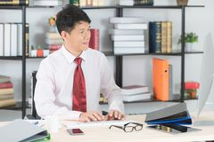 Asian business man at office. Happy middle aged, handsome, Asian, businessman, in white shirt, dark red necktie, working in his startup office, sending emails royalty free stock photo