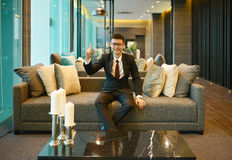Asian Business man pointing on sofa in luxury condo Royalty Free Stock Images