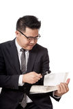 Asian business man read a book with  magnifying glass Stock Photos