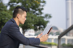 Asian Business man reading a newspaper. Royalty Free Stock Photos