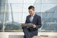 Asian Business man reading a newspaper. Royalty Free Stock Photo