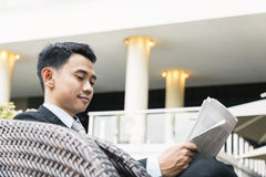 Asian Business man reading a newspaper Royalty Free Stock Photo
