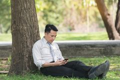 Asian business man relaxing in the park after work. He looking p. Hone enjoying the shadow of the tree in a sunny day. businessman relieving, rest time concept Stock Photo