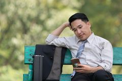 Asian business man relaxing in the park after work. He looking p. Hone enjoying the shadow of the tree in a sunny day. businessman relieving, rest time concept Royalty Free Stock Photography