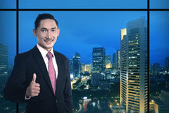 Asian business man show thumb up. Over night city background Royalty Free Stock Image