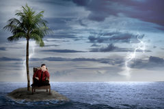 Asian business man sit on the chair, alone on the small island Stock Photos