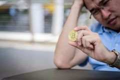 Asian business man sitting in depression with bit coin money. The asian business man sitting in depression with bit coin money Royalty Free Stock Photos