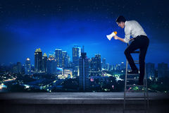 Asian business man standing on the ladder, holding megaphone Royalty Free Stock Photo