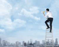 Asian business man standing on the ladder, holding megaphone Stock Photo