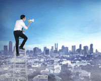 Asian business man standing on the ladder, holding megaphone Stock Image