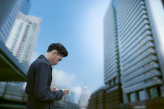 Asian business man standing and use smartphone with business bui Stock Photography