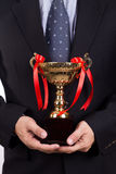 Asian business man in suit holding golden trophy. On white background stock photography