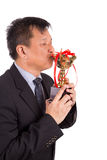 Asian business man in suit kissing golden trophy Royalty Free Stock Photos