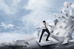 Asian business man surfing on the wave of papers. Business challenge concept Royalty Free Stock Photos