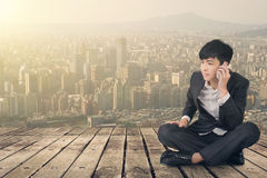 Asian business man take a call and sit on ground Stock Photo