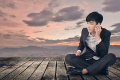 Asian business man take a call and sit on ground Royalty Free Stock Image