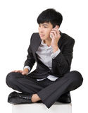 Asian business man take a call and sit on ground. Royalty Free Stock Image