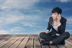 Asian business man take a call and sit on ground Royalty Free Stock Images
