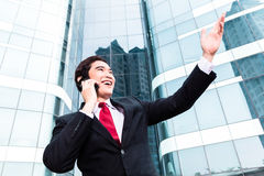 Asian business man talking outside to mobile phone Royalty Free Stock Images