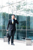 Asian business man talking to cell phone outside Stock Photos
