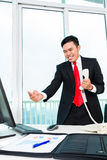 Asian business man telephoning in office. Controlling profit Royalty Free Stock Photos
