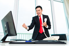 Asian business man telephoning in office. Controlling profit Royalty Free Stock Photography