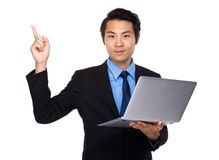 Asian Business man use of laptop and finger point up Royalty Free Stock Photo