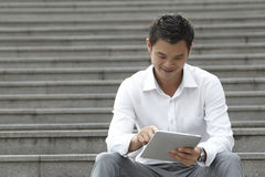 Asian Business man using a Digital Tablet Stock Image