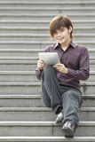 Asian Business man using a Digital Tablet Stock Photo