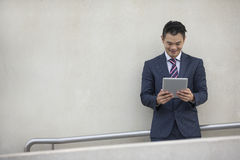 Asian business man using digital tablet. Royalty Free Stock Images