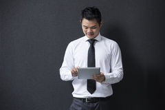 Asian business man using digital tablet computer, leaning against a black wall. Stock Photos