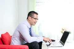 Asian business man using laptop computer with happiness Royalty Free Stock Image