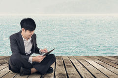 Asian business man using pad and sit on ground Royalty Free Stock Photo