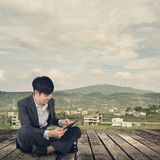 Asian business man using pad and sit on ground Stock Image