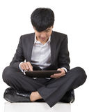 Asian business man using pad and sit on ground Royalty Free Stock Image