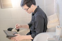 Asian business man using tablet in toilet. Young Asian business man using digital tablet and pen on water closet in toilet or bathroom. Home living lifestyle stock image