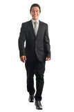 Asian business man walking. Full body front view portrait of handsome young Southeast Asian businessman walking, isolated on white background Stock Image