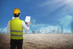 Asian business man wear yellow helmet looking blueprint to build. Back view of asian business woman wearyellow helmet looking blueprint to build office building Stock Photo