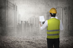 Asian business man wear yellow helmet looking blueprint to build. Back view of asian business woman wearyellow helmet looking blueprint to build office building Royalty Free Stock Images