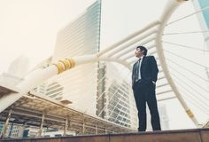 An Asian business man wearing a black suit. Standing with determination in the city.Concepts in Business Intention. stock photos
