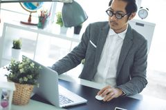 Asian business man wearing eyeglass in office. Businessman working on laptop computer in the office, Asian business man wearing eyeglass in office stock image