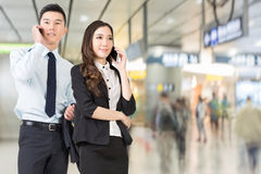 Asian business man and woman talking on cellphone Stock Photo