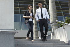 Asian Business Man and Woman Walking Down Steps Stock Photo