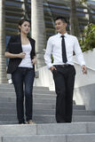 Asian Business Man and Woman Walking Down Steps Stock Image