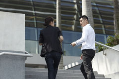 Asian Business Man and Woman Walking up Steps Stock Images